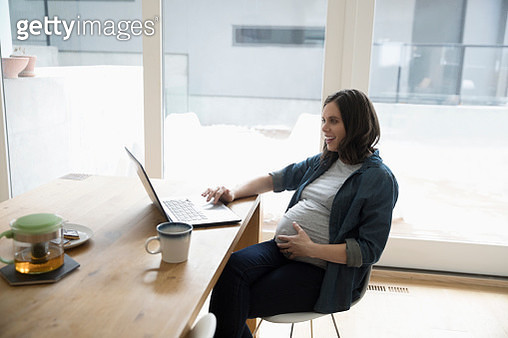Pregnant woman working at laptop at dining room table - gettyimageskorea