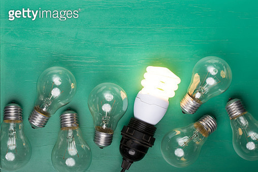 Incandescent lightbulbs laying next to one glowing, energy efficient lightbulb. - gettyimageskorea