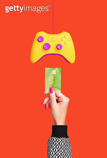 Female, white hand inserting credit card into games console shot on red background. - gettyimageskorea