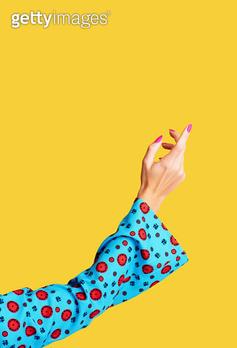 Female arm in blue sleeve and with painted nails shot on yellow background. - gettyimageskorea