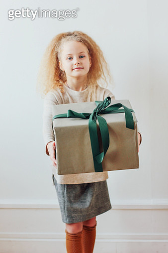 Portrait Of Girl Holding Christmas Present Against Wall - gettyimageskorea