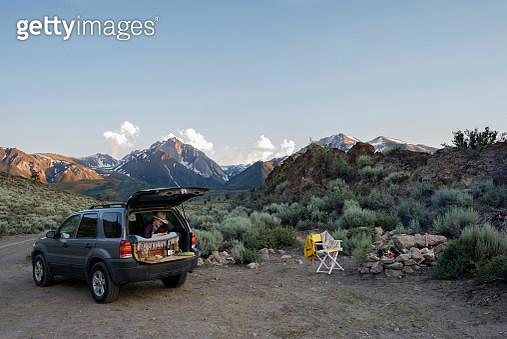 Female hiker sitting in sports utility vehicle against Mount Morrison - gettyimageskorea