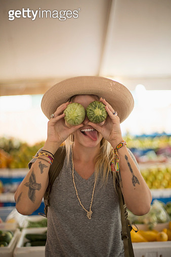 Caucasian woman making a face with fruit in farmers market - gettyimageskorea
