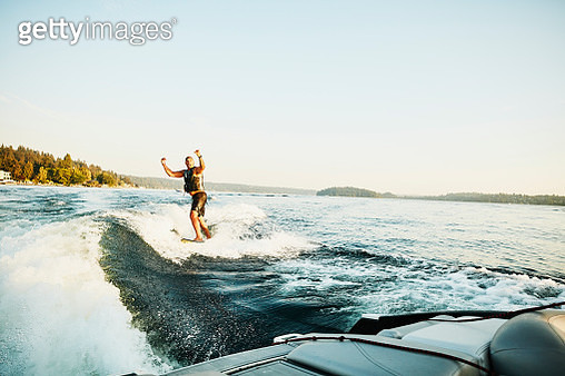 Smiling man celebrating while wake surfing on summer evening - gettyimageskorea