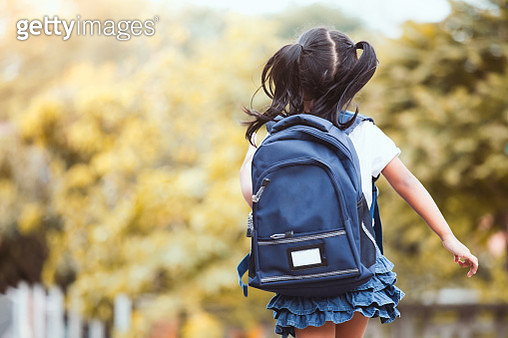 Rear View Of Girl Wearing Backpack While Walking Against Trees - gettyimageskorea