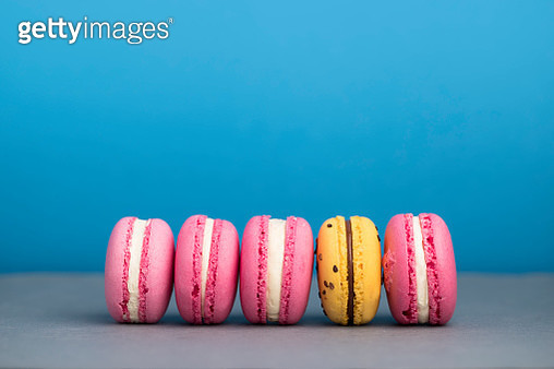 Row of pink macaroons with one yellow macaroon. - gettyimageskorea