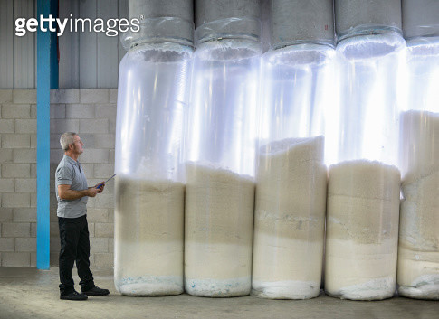 Worker using air cleaner and recycling machinery in textile mill - gettyimageskorea