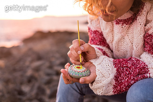 Midsection Of Woman Painting Pebble While Sitting At Beach During Sunset - gettyimageskorea