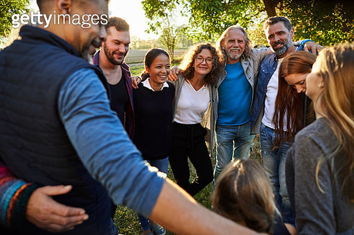 Group of happy people embracing on a garden party at sunset - gettyimageskorea