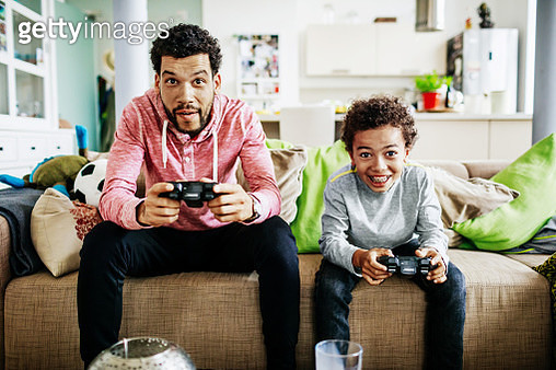 A father and son are concentrating while sitting down at home playing video games together. - gettyimageskorea