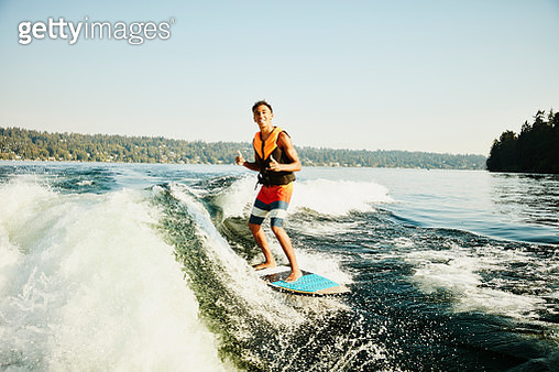 Smiling teenage boat making thumbs up gesture while wake surfing on summer afternoon - gettyimageskorea