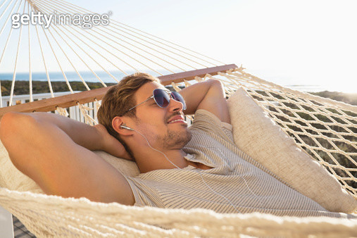 Young man listening music and relaxing in hammock - gettyimageskorea