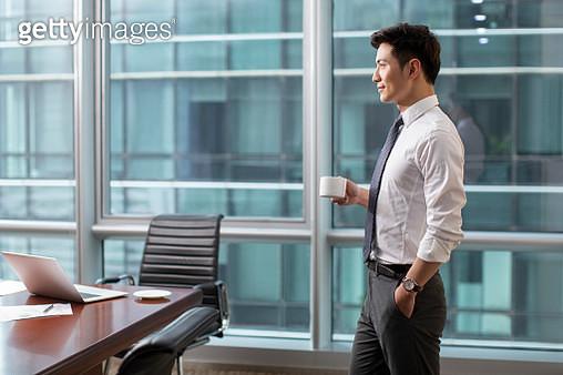 Confident businessman drinking coffee - gettyimageskorea