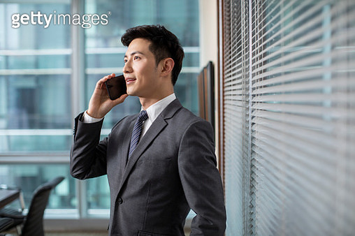 Confident businessman using smartphone in office - gettyimageskorea