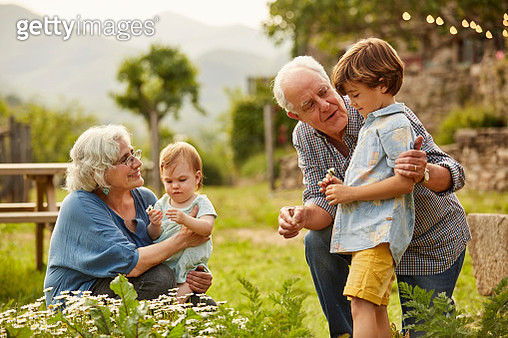 Grandparents talking to children. Family having leisure time in yard. They are wearing casuals. - gettyimageskorea