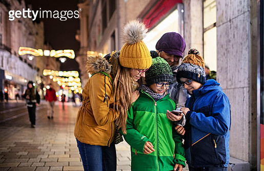 Mother with three kids sightseeing city of Brno. checking map in smartphone in Wroclaw main square. Family is sightseeing the city on cold autumn day evening. Sightseeing is fun even in the bad weather! - gettyimageskorea