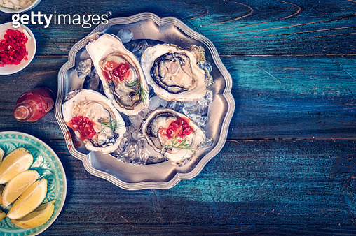 Oysters on plate with Tabasco sauce and lemon - gettyimageskorea