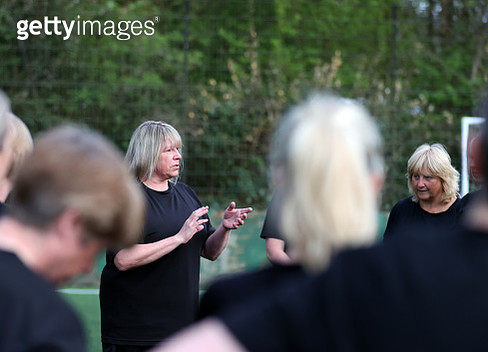 Female soccer coach discussing strategy with female soccer team - gettyimageskorea