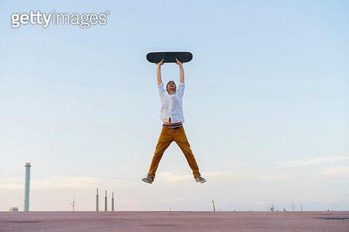 Young man jumping in the air holding a skateboard - gettyimageskorea