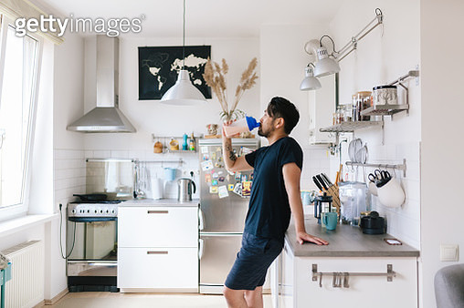 Asian man drinks protein shake after home workout - gettyimageskorea