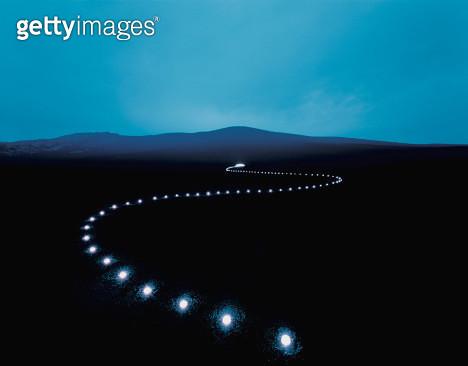 Row of strobe lights across volcanic landscape, dusk - gettyimageskorea