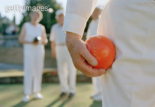 Elderly man holding ball in game of lawnbowling, close-up - gettyimageskorea