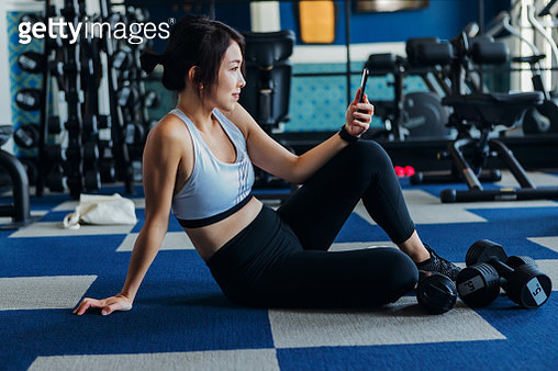 Side view of young athletic Asian woman using exercise tracking app on smartphone to monitor her training progress after exercising at hotel gym - gettyimageskorea