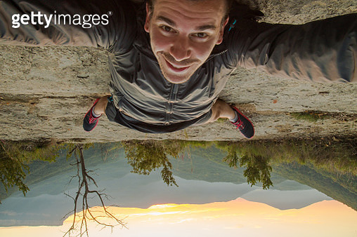 30 years man smiling taking a selfie up side down on the ground with the beautiful nature views of the Garrotxa region on sunrise moment with the morning light and the mountains. - gettyimageskorea