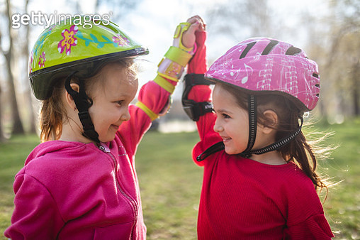 Sisters spending time together at the park roller skating - gettyimageskorea
