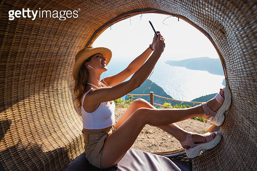 Beautiful young woman relaxing on the beach. She is posing and pensive looking away with smile on her face - gettyimageskorea