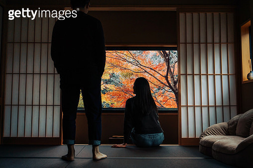 A loving young Asian couple relaxing in a traditional Japanese style apartment, chatting and enjoying the beautiful nature Autumn scenics during the day - gettyimageskorea