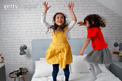 Two friends jumping on bed together - gettyimageskorea