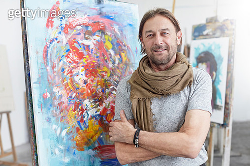 Portrait smiling, confident artist standing at abstract painting in art class studio - gettyimageskorea