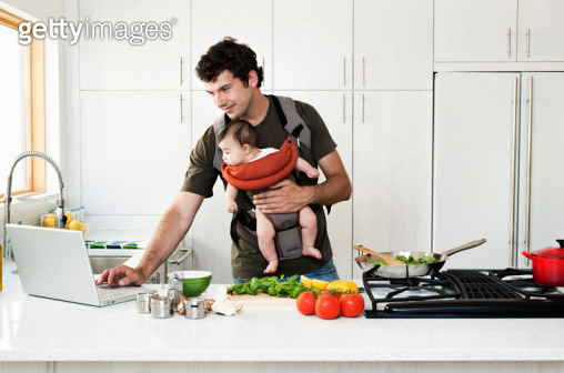 Man cooking while holding baby.  Checking recipe on computer - gettyimageskorea