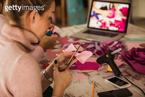 Cutting out flower petals while crafting decorative paper flowers - gettyimageskorea