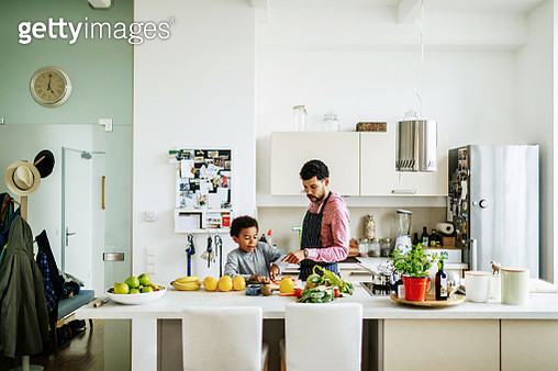 A father and son at home in the kitchen helping each other prepare some lunch. - gettyimageskorea