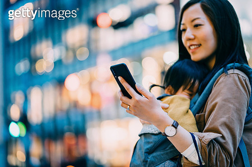 Young Asian mother using smartphone in downtown city street while shopping with little daughter - gettyimageskorea