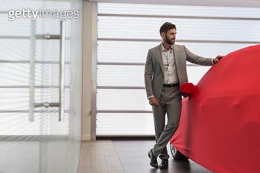 Car salesman standing at covered car in car dealership showroom - gettyimageskorea