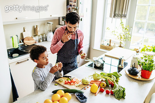 Single dad spending some time with his son, snacking while they prepare some lunch together. - gettyimageskorea