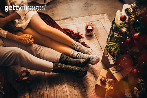 Couple holding hands and relaxing sitting under Christmas tree - gettyimageskorea