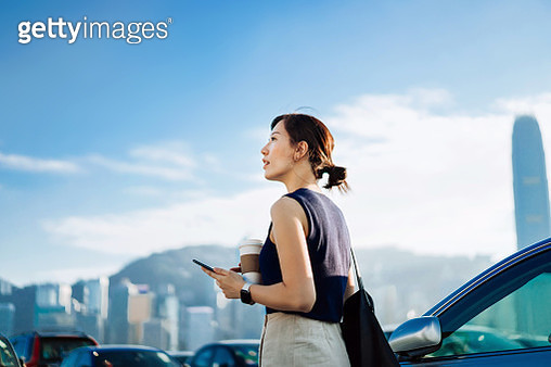 Confidence and professional young Asian businesswoman walking out of her car, holding smartphone and a cup of coffee. Looking towards the sky against urban cityscape. Business on the go concept - gettyimageskorea