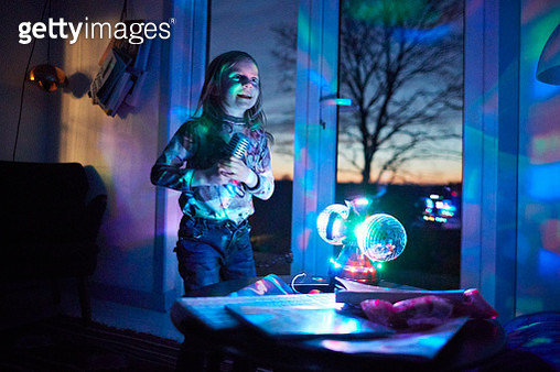 Happy girl with microphone singing in living room with disco ball - gettyimageskorea