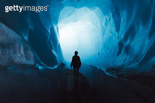 Silhouette of woman tourist walking inside the beautiful turquoise colored ice cave inside of Rhone glacier in Swiss Alps - gettyimageskorea