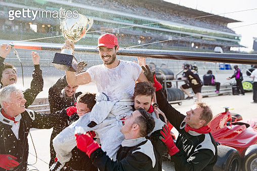Formula one racing team carrying driver with trophy on shoulders, celebrating victory on sports track - gettyimageskorea