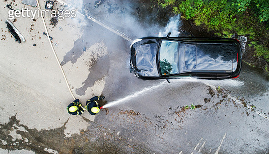 Two Firefighters Extinguishing A Burning Car After An Accident. - gettyimageskorea