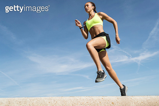 Low angle view of young female runner running along sea wall against blue sky - gettyimageskorea