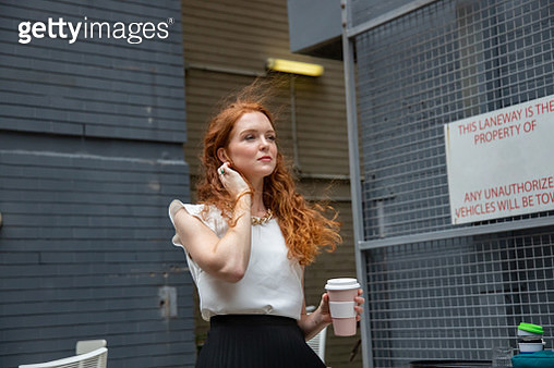 Young professional women waits with coffee in environmental friendly reusable cup while standing - gettyimageskorea