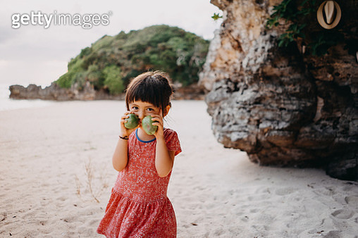 Cute toddler girl smelling guavas and smiling at camera on beach - gettyimageskorea