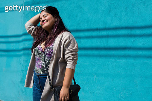 Portrait of a beautiful latina woman standing in front of a blue wall. - gettyimageskorea