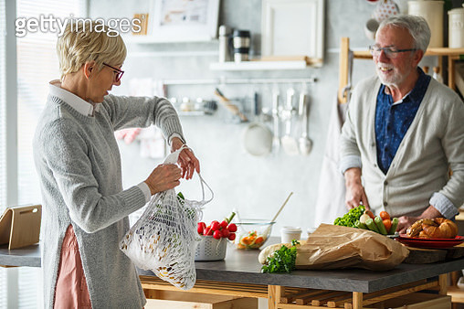 Senior woman coming home with fresh groceries, while her husband prepares breakfast. - gettyimageskorea